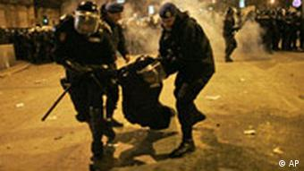 Police carry an injured colleague after riots in Belgrade