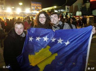 Kosovars hold the new national flag as they celebrate Kosovo's declaration of independence