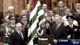 New president of Georgia's breakaway Abkhazia region Sergei Bagapsh holds the separatist region's flag during his inauguration