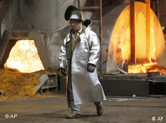A worker walks in front of a furnace at a steel factory