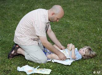 A father putting a diaper on a child