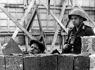 Ein Schwarz-Weiß-Bild von einem Soldaten der Nationalen Volksarmee, der einen Bauarbeiter bei der Reparatur der Berliner Mauer beaufsichtigt.