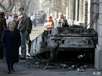 A woman walking by a burnt car in Belgrade