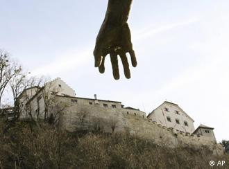 The hand of a monument reaches out towards the castle of Vaduz, Liechtenstein,
