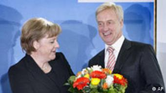 Merkel hands over a bunch of flowers to the Christian Democratic top candidate Ole von Beust in Berlin, Germany, Monday, Feb. 25, 2008
