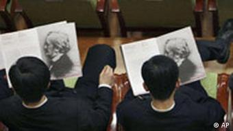 North Koreans look through the performance program before the start of a concert by the New York Philharmonic in Pyongyang, North Korea on Tuesday, Feb. 26, 2008