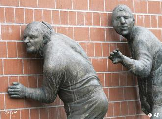 Sculpture of two people listening with their ears pressed to a wall