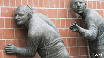 Sculptures of people listening to a wall