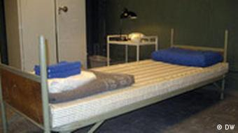 A steel-framed bed, with a thin matress and neatly folded sheets and blankets stands in front of a plain grey locker