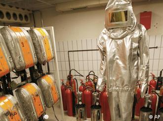 View of decontamination equipment, including a silver body suit and orange air tanks hanging in a row