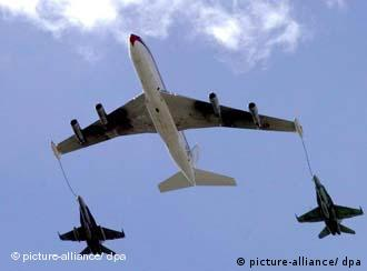 A Boeing 707 tanker plane with two F-18 jet fighters of the Spanish Air Force connected to refueling hoses