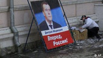 People pass by a poster of Russian First Deputy Premier and presidential hopeful Dmitry Medvedev in downtown Vladivostok