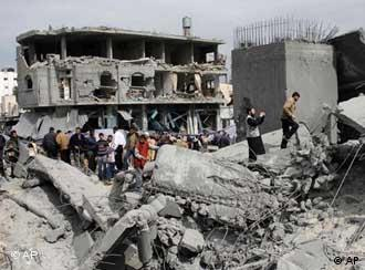 Palestinians gather next to the rubble of a mosque that was part of a compound used by the security forces of Hamas the day after it was hit in an Israeli missile strike in Rafah, southern Gaza Strip, Sunday, March 2, 2008.