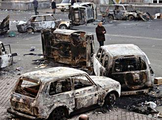 A man walks among burned cars, left after night riots, in downtown Yerevan on Sunday morning, March 2, 2008. Protesters in Armenia's capital largely dispersed Sunday after the president imposed a sweeping, 20-day state of emergency and their leader appealed for calm.