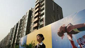 A Chinese woman stands in front of apartment buildings inside the Olympic Village