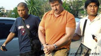 Victor Bout with two undercover police officers