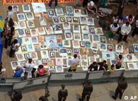 Defensores de derechos humanos despliegan fotos de las víctimas en Medellín.