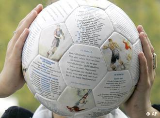Ein Fußball mit Literaturzitaten und Bildern von Fußballspielern, der von zwei Händen vor ein Gesicht gehalten wird