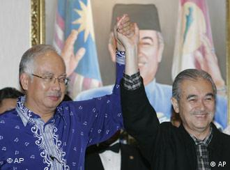 Malaysia's Prime Minister Abdullah Ahmad Badawi, right, holds hands with Najib Razak, deputy Prime Minister on March 9, 2008 when they suffered significant losses in the general election