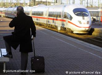 A man waits with his luggage on a rail platform