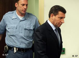 Former Croatian General Ante Gotovina, right, enters the courtroom for his initial appearance at the Yugoslav war crimes tribunal in The Hague, the Netherlands, Monday Dec. 12, 2005. Gotovina is indicted on seven counts of crimes against humanity for the killings of at least 150 Serbs by troops under his command, the expulsion of tens of thousands of others and the destruction and pillaging of at least 11 Serb villages during the closing months of the Croatian war in 1995. Gotovina was third on the tribunal's most wanted list, preceded only by Bosnian Serb leader Radovan Karadzic and his top commander Ratko Mladic. (AP Photo/Ed Oudenaarden, Pool)