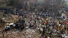 Pakistani rescue and security officials examine the site of a bomb explosion at the office of the Federal Investigation Agency in Lahore, Pakistan on Tuesday, March 11, 2008. Bombs hit a federal police headquarters and a house in the eastern city of Lahore on Tuesday, killing at least 15 people and wounding many more, police said. (AP Photo/K.M. Chaudary)