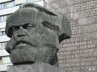 The statue of Marx's head stands against a grey brick building
