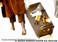 Женщина везет чемодан на колесиках