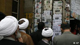 People including clerics, read newspapers on the wall, in Qom, Iran, in March 2008