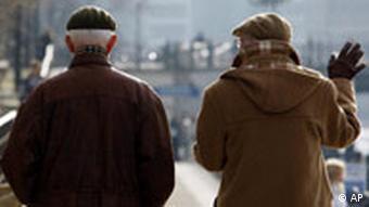 Two older men walk along a river