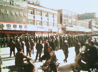 In this image taken with a mobile device, made available by the Indian Branch of Students for a Free Tibet, which purports to show pedestrians walking amid Chinese law enforcement, Friday, March 14, 2008, in Sangchu County, Kanlho Tibetan Autonomous Prefecture, Gansu Province, China. The area is traditionally known to Tibetans as Amdo Labrang. (AP Photo/Indian Branch of Students for a Free Tibet, TCHRD) ** NO SALES **