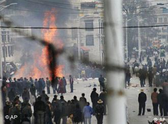 Protesters gather around burning debris in the streets of Lhasa, Tibet