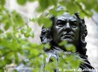Durch die grünen Blätter eines Baumes sieht man den Kopf der Bach-Statue