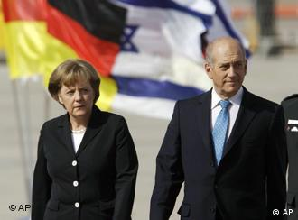 German Chancellor Angela Merkel, left, and Israel's Prime Minister Ehud Olmert, right, at the official welcoming ceremony for Merkel at Ben Gurion airport in Tel Aviv, Sunday March 16, 2008. Merkel will spend three days touring the Jewish nation and strengthening ties between Berlin and Jerusalem. (AP Photo/Ariel Schalit)