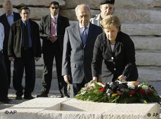 German Chancellor Angela Merkel, right, is flanked by Israel's President Shimon Peres, 2nd right, as she lays down a wreath at the grave of Ben Gurion at Sde Boker in Israel's Negev desert, on Sunday March 16, 2008. The German Chancellor is on a three-day official visit to Israel. (AP Photo/Markus Schreiber)