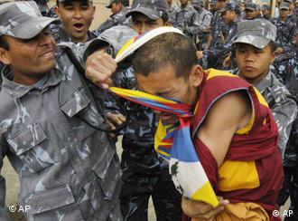 Nepalese police officers snatch a Tibetan flag from a Tibetan protester demonstrating in front of the UN office in Kathmandu