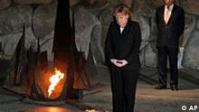 German Chancellor Angela Merkel, left, pauses after laying a wreath at the Hall of Remembrance, as Israel's Prime Minister Ehud Olmert, right, looks on during a visit to the Yad Vashem Holocaust Memorial in Jerusalem, Monday, March 17, 2008. Merkel is on a three day official visit to Israel. (AP Photo/Sebastian Scheiner)