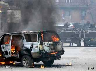 A UN vehicle burns in the street after riots swept through Mitrovica
