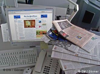 Газеты возле компьютера с открытим вебсайтом
