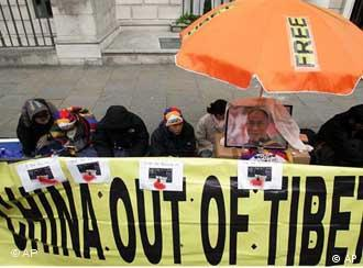 Tibetan students sit during a hunger strike vigil outside the Chinese Embassy in London,