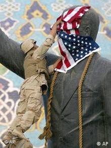 A US soldier puts a US flag over a large statue of Saddam Hussein