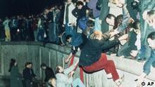 Ostberliner erklettern den Antifaschistischen Schutzwall in Berlin, noember 1989