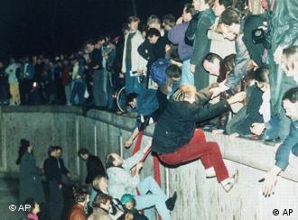 Mauerfall Berlin - Menschen klettern über die Mauer (Foto: AP)