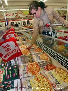 Eine junge Frau nimmt Tiefkühlpizza aus der Kühltruhe (Foto: pa/dpa)