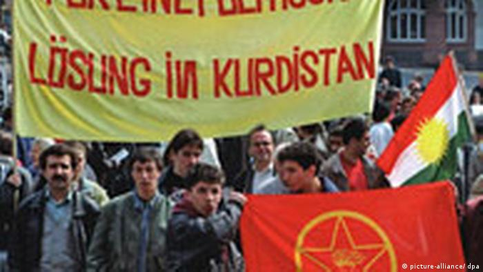 Kurdish demonstrators holding a banner reading'For a political solution in Kurdistan