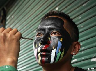 An exile Tibetan gets his face painted for a protest march in Dharmsala, India