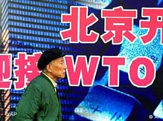 Ein chinesischer Mann läuft vor einem Plakat mit WTO-Aufschrift
