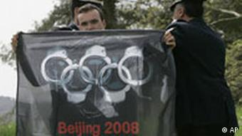 Policemen detain a protester as he holds a banner at the beginning of the flame-lighting ceremony for the Beijing 2008 games in ancient Olympia, Greece, on Monday March 24, 2008