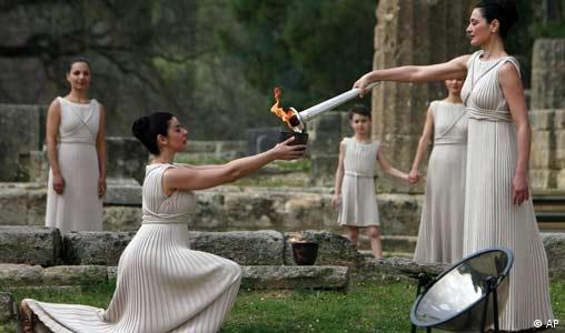 Greek actress Maria Nafpliotou, playing the role of a high priestess, passes on the Olympic flame lit with a concave mirror to another priestess, near the Temple of Hera in Ancient Olympia