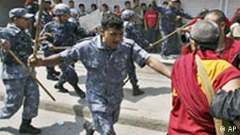 Policemen chase away protesters as Tibetans demonstrate against Chinese rule in Tibet, outside the Chinese visa office in Katmandu, Nepal